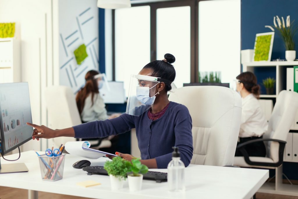 African marketing specialist at workplace wearing face mask
